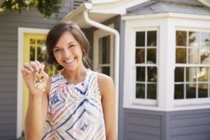 Young woman holding keys in front of house